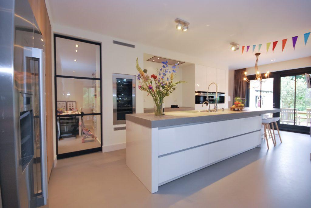 Maatwerk witte hoogglans greeploze keuken met een ingebouwde kastenwand en handgemaakte eikenhouten fronten