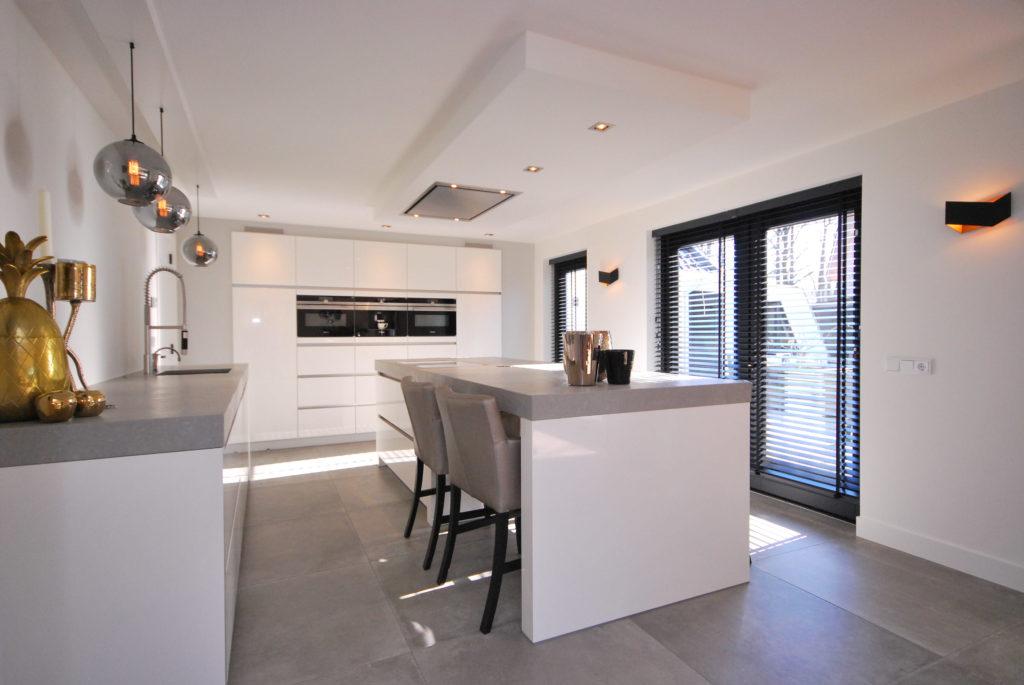 Moderne hoogglans keuken met apparatenwand en kookeiland